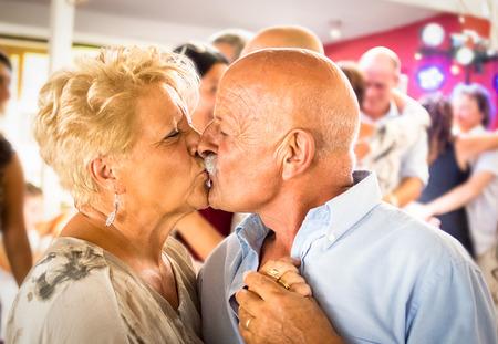 Felice anziano coppia di pensionati divertirsi a ballare al ristorante celebrazione del matrimonio partito - Amore concetto di lifestyle anziani e la pensione con l'uomo bella moglie kissing - immagine a colori ad alta ISO Archivio Fotografico - 67624523