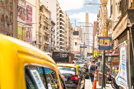 corrientes: BUENOS AIRES, ARGENTINA - NOVEMBER 17, 2016: yellow taxi cab in rush hour and traffic jam congestion on Avenida Corrientes in downtown area in argentinian capital city - Warm afternoon color tones