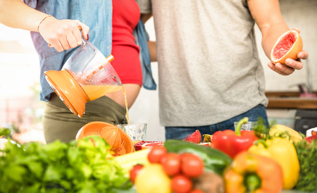 juice squeezer: Young couple with pregnant woman at cooking in kitchen with healthy vegetarian food - Love food concept with people at home preparing vegan lunch with bio vegetables - Focus on pressed juice squeezer Stock Photo