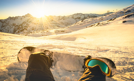 Snowboarder sitting on relax moment at sunset in Les Deux Alpes ski resort - Winter sport concept with person on top of the mountain ready to ride down - Legs view point with warm backlighting filter