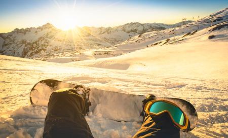 Snowboarder assis sur détendre un moment au coucher du soleil dans Les Deux Alpes station de ski - concept de sport d'hiver avec personne au-dessus de la montagne prêt à rouler vers le bas - Jambes Point de vue avec filtre rétro-éclairage chaud