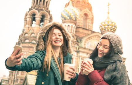 """Glückliche Freundinnen nehmen Winter selfie bei """"Erlöser auf Spilled Blood"""" -Kirche in Sankt Petersburg - Freundschaft Konzept mit Mädchen Spaß zusammen Kaffee im Freien zu trinken - Focus on left young woman"""