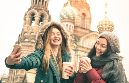 russian church: Happy girlfriends taking winter selfie at  Savior on Spilled Blood  church in Saint Petersburg - Friendship concept with girls having fun together drinking coffee outdoor - Focus on left young woman