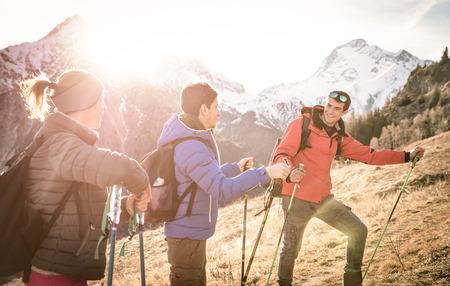 Gruppo di amici di trekking sulle Alpi francesi al tramonto - escursionisti con zaini e bastoni da passeggio su montagna - Wanderlust concetto di viaggio con i giovani a un'escursione nella natura selvaggia - Focus su ragazzo giusto