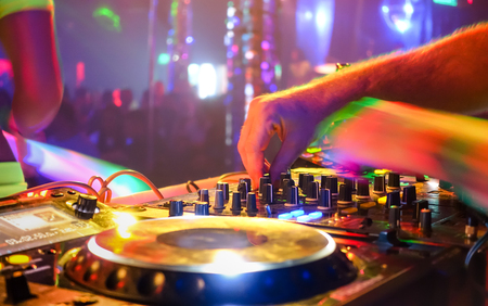 party system: Close up of dj playing party music on modern cd usb player in disco club - Nightlife and entertainment concept  - Defocused background with shallow depth of field and focus on buttons near mixing hand