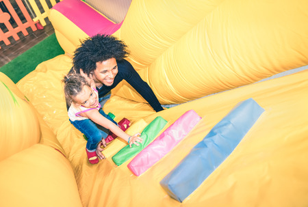 slide: Latin american dad playing with mixed race daughter on inflatable slide at kindergarten playroom - Family concept with happy multiracial child and father having fun together at kids playground toyroom