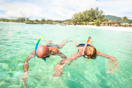 Senior couple vacationer swimming together on tropical Koh Lipe sea in Thailand - Snorkeling tour in exotic scenario - Active elderly and travel concept around world - Warm turquoise filter color tone Stock Photo
