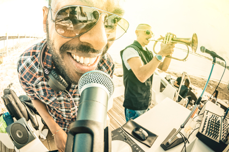 festival moment: Dj playing summer hits at sunset beach party with trumpet jazz performer - Vacation concept at open air club with house music at spring break location - Fisheye lens with vintage sunshine filter