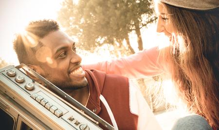 garcon africain: deux multi-ethnique au début de l'histoire d'amour écoute de la musique sur un enregistreur stéréo radio - relation de race mixte Urban concept avec des jeunes ayant du plaisir en plein air - chaud filtre cru désaturé