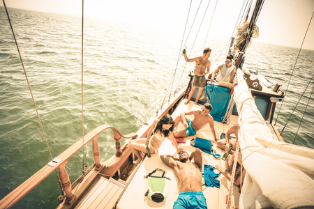 hopping: Happy multiracial friends having fun at sail boat trip party with dj set - Friendship concept with young multi racial people on sailboat - Travel lifestyle on exclusive location - Warm retro filter Stock Photo