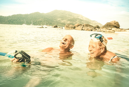 vacationer: Senior couple vacationer having genuine fun on tropical Koh Lipe sea in Thailand - Snorkel tour in exotic scenario - Active elderly and travel concept around world - Warm desaturated greenery filter Stock Photo