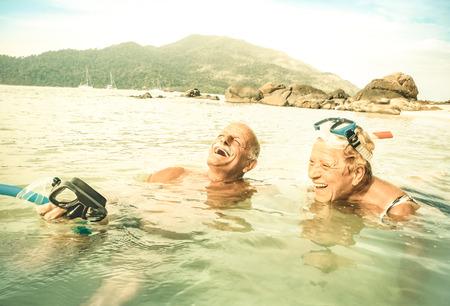 Senior couple vacationer having genuine fun on tropical Koh Lipe sea in Thailand - Snorkel tour in exotic scenario - Active elderly and travel concept around world - Warm desaturated greenery filter Imagens