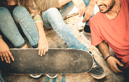 youth group: Group of multiracial friends having fun and spending time together at skate board park  - Youth friendship concept with young people sharing skateboard outdoors - Vintage retro desaturated filter Stock Photo