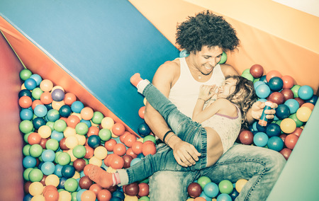 father daughter: Latin american dad playing with mixed race daughter on ball pit swimming pool at kindergarten playroom - Family concept with happy multiracial child and father having fun at kid toyroom - Retro filter
