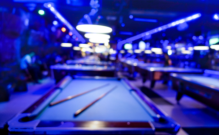 billiards room: Defocused background of billiard playroom - Blurred composition of pool game saloon with dominant blue color tones and incandescent neon light - Fun and entertainment concept with blurry dark backdrop Stock Photo