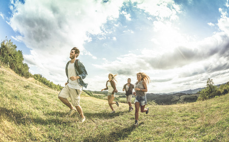 airiness: Group of friends running free on grass meadow - Friendship and freedom concept with young happy people moving free at camping experience - Vintage desaturated filter with backlight contrast sunshine