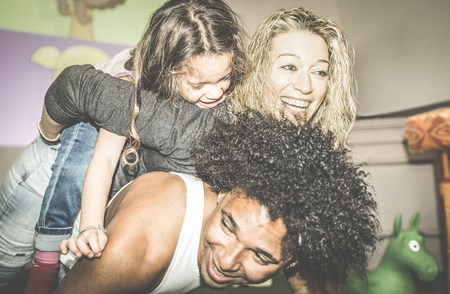 Happy multiracial mom and dad playing with mixed race daughter at kindergarten playroom - Multicultural family concept with happy child having fun with father and mother at kid toyroom - Retro filter Stock Photo