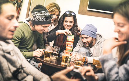 Happy friends playing table board game while drinking beer at pub - Cheerful people having fun at brewery bar corner - Friendship concept on contrast desaturated filter with soft greenery color tones