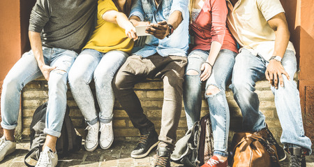 Group of multiculture friends using smartphone on urban background - Technology addiction concept in youth lifestyle disinterested to each other - Always connected people on modern mobile smart phones
