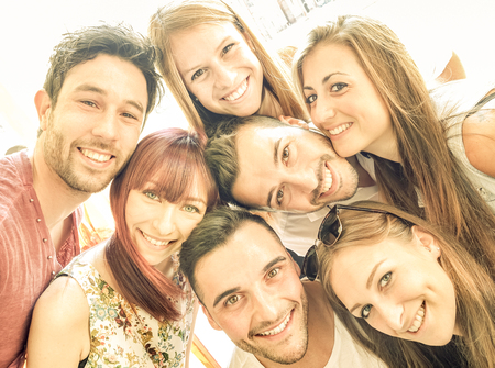 holiday gathering: Happy best friends taking selfie outdoors with spring time backlighting - Friendship and happiness concept with young people having fun together - Warm vintage filter with bright sunshine color tones