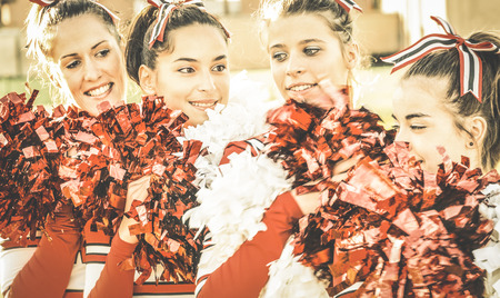 Group of cheerleaders at university sport event show - Concept of unity and team sport with active girls - Training at college high school with young female teenagers - Warm desaturated retro filter Stock Photo