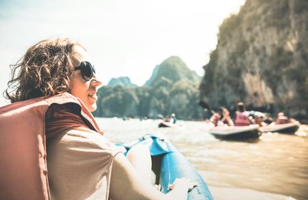 Jonge vrouw reiziger met reddingsvest te genieten van de zonsondergang ritje op kayak island hopping - Wanderlust en reizen concept avontuur meisje toeristische reiziger op excursie in Thailand - Retro zon filter