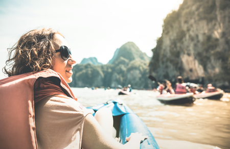 Young woman traveler with life jacket enjoying sunset ride on kayak island hopping - Wanderlust and travel concept with adventure girl tourist traveler on excursion in Thailand - Retro sunshine filter