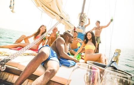 Groep multiraciale vrienden die plezier hebben op zeilbootfeest met dj-set - Vriendschapsconcept met jonge multi-raciale mensen op zeilboot - Reis lifestyle op exclusieve atmosfeer - Warm helder filter
