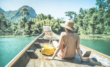 Young woman traveler on longtail boat trip at island hopping in Cheow Lan Lake - Wanderlust and travel concept with adventure girl tourist wanderer on excursion in Thailand - Retro turquoise filter 스톡 콘텐츠