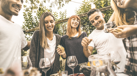 Happy friends having fun drinking red wine eating at garden party - Friendship concept together at farmhouse vineyard winery - Focus on girl in middle with retro desaturated opaque contrast filter