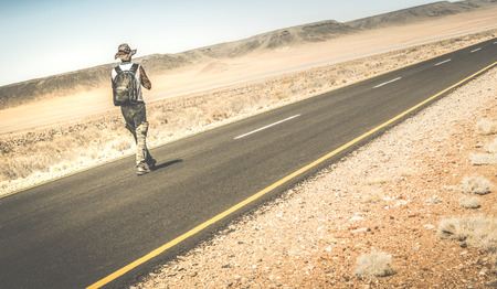 lonely: Man walking on the road on namibian african desert - Alternative lifestyle concept and wanderlust experience with guy backpacking to unknown - Travel trip adventure around the world - Retro filter
