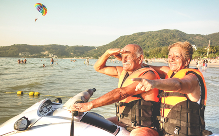 Senior happy couple having fun on jet ski at beach island hopping tour - Active elderly and travel concept around the world with retired people riding water scooter jetski - Warm vintage vivid filter Stock Photo