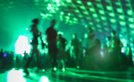 entertainment event: Abstract blurred people moving on and dancing at music night festival event - Defocused image of disco club party with laser show - Nightlife entertainment concept - Vivid greenery filter Stock Photo