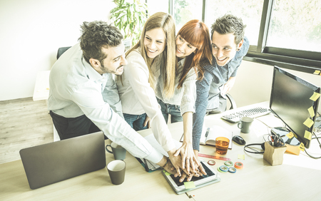 working hands: Group of young people employee coworkers stacking hands in urban coworking place studio - Human resources business concept at working time - Start up entrepreneurs at office - Bright greenery filter Stock Photo