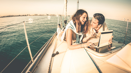 Young couple in love on sail boat having fun with tablet - Happy luxury lifestyle on yacht sailboat - Technology interaction with satellite wifi connection - Retro contrasted filter Stok Fotoğraf - 72633142