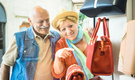 Senior couple shopping at fashion bag store with wife pointing showcase to husband - Active elderly concept with mature man and woman having fun in city - Happy retired people moments on vivid colors