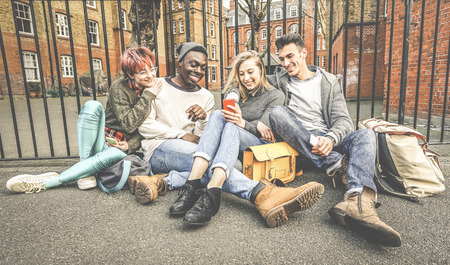 Group of happy multiracial best friends having fun using mobile smart phone - Young hipster people addicted by smartphone on social network community - Technology concept - Vivid saturated color tones Stock Photo
