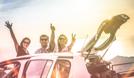 Group of best friends cheering on car road trip at sunset - Happy people outdoor on vacation tour adventure - Friendship concept at travel together around world - Soft focus with vintage color filter