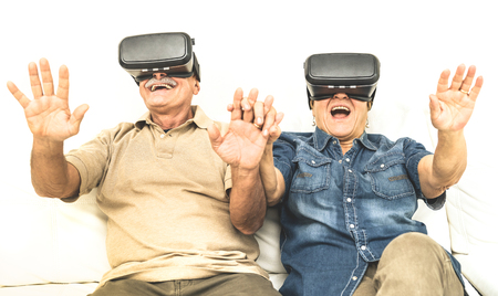 technology trends: Senior mature couple having fun together with virtual reality headset sitting on sofa - Happy retired people using modern vr goggle glasses - New trends and technology concept and funny active elderly