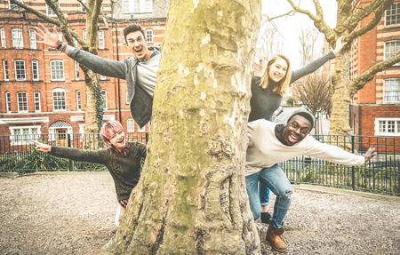 Multiracial fancy friends having fun outdoors at city park in Shoreditch London - Friendship youth concept with young happy people hanging out together - Retro contrast filter with shadow color tones
