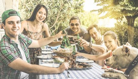 amis heureux de se amuser manger et grillage ensemble à la cour jardin barbecue - Amitié et le concept de la famille avec les jeunes appréciant la nourriture et de la bière à la maison barbecue pique-nique parti - filtre Retro