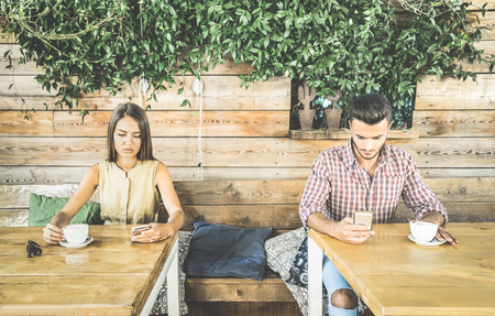 boyfriends: Fashion couple in disinterest moment ignoring each other using mobile cell phone - Concept of apathy sadness addicted to new technologies - Boyfriend and girlfriend break up with smartphones addiction