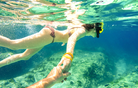 scenarios: Snorkel couple swimming together in tropical sea with follow me composition - Snorkeling tour in exotic diving scenarios - Fun travel concept with active girl underwater - Soft focus due water density