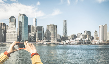 Tourist hands taking pic of New York City skyline from water taxi tour on river Hudson with digital pocket camera - Wanderlust concept and travel lifestyle around the world - Retro contrasted filter Stock Photo