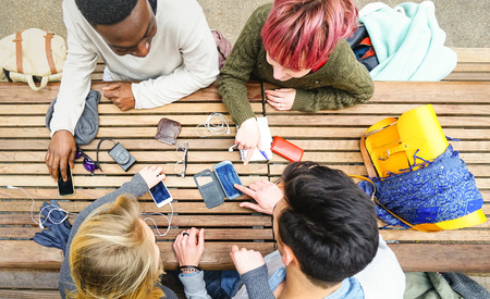 Top view of multiracial friends using mobile smart phone - Addiction concept with young people on new tech devices - Multicultural students having fun on social media networking - Warm vivid filter 스톡 콘텐츠