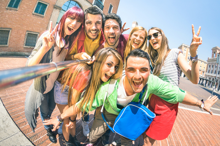 Group of multicultural tourists friends having fun taking selfie and shouting out at old town tour -Travel lifestyle concept with happy people wandering around city landmarks - Vivid saturated filter Stockfoto