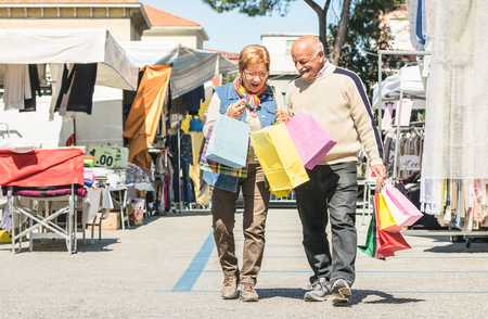 Senior couple shopping together at flea market with wife watching in husband bags
