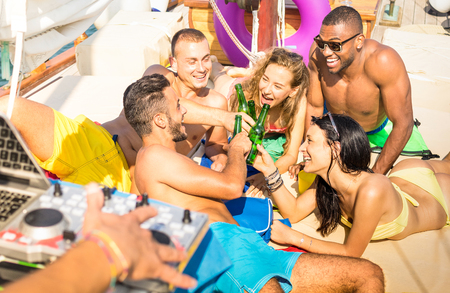 Friendship concept with young multi racial people toasting beer on sailboat - Travel lifestyle on warm vivid filter