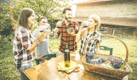 Happy friends having fun drinking at winery vineyard - Friendship concept with young people enjoying harvest together at farmhouse - Red wine tasting indie experience outdoors - Vintage retro filter