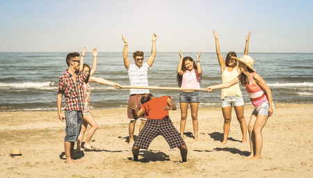 다인종 해변에서 림보 게임과 함께 행복 친구 그룹 재미 - 여름 기쁨과 젊은 멀티 민족 사람들이 봄 방학 휴가 연주와 우정 개념 - 레트로 빈티지 필터